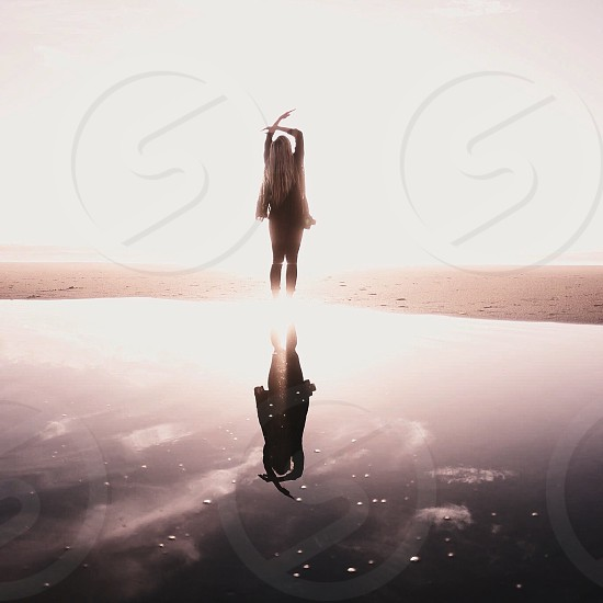 back of a woman with long blonde hair raising her arms to the sky standing over glassy water under the sun photo