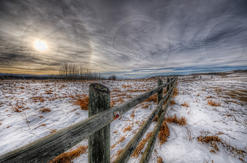 black and brown wooden fence surrounded by snow covered field photo