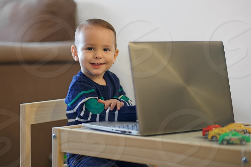Baby kid toddler playing and browsing laptop computer Closeup portrait of little boy exploring notebook new generation concept photo