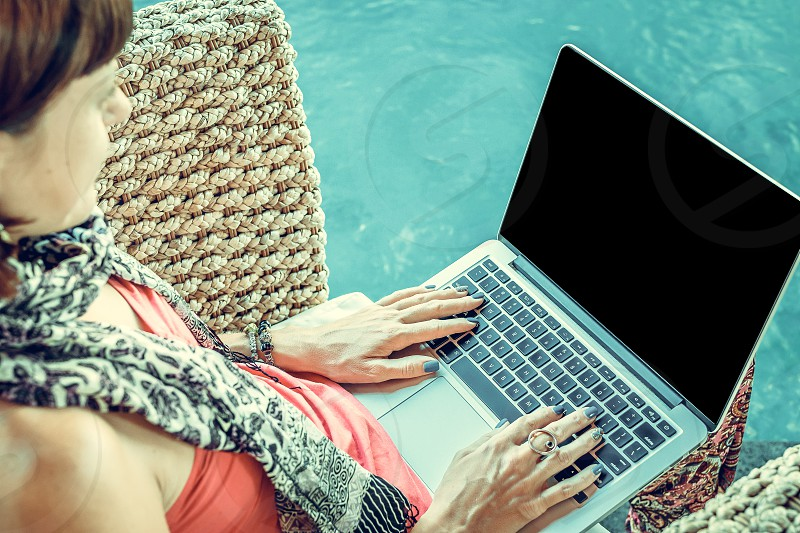 Sexy woman using laptop computer on a lounge near swimming pool outdoors. Tropical garden of Bali island Indonesia. photo