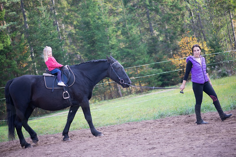 A little girl  rides a horse for the first time in his life. photo