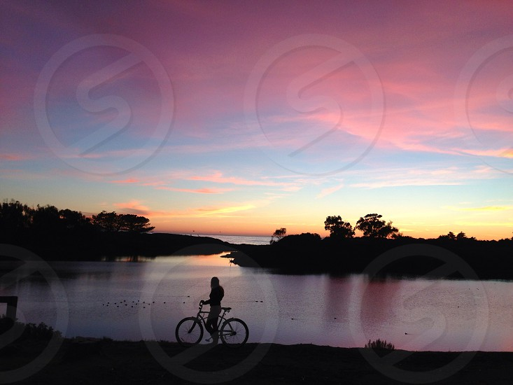 person with bicycle silhouette by the river side photo