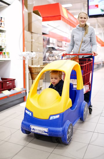 Child friendly supermarket shopping with a young mother pushing her small son in a colourful plastic car attached to the shopping trolley keeping him happy and entertained while she buys the groceries photo