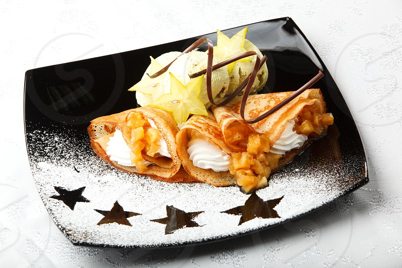Golden pancakes with carambola and whipped cream served with scoops of ice cream and topped with a chocolate whirl in a decorative plating with icing sugar star patterns photo