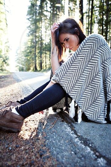 woman wearing brown boots sitting on the road photo