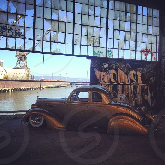 gold classic car warehouse overlooking water photo