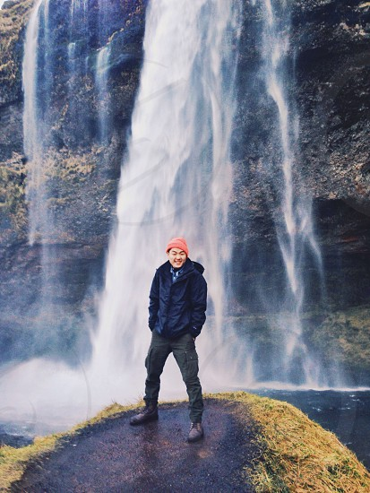 man standing on rock with waterfalls background photo
