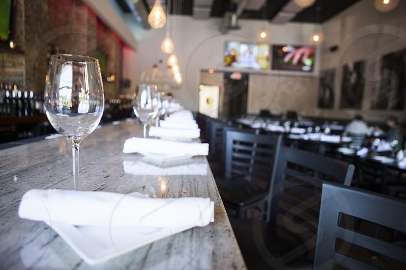 white table napkin folded beside clear wine glass photo