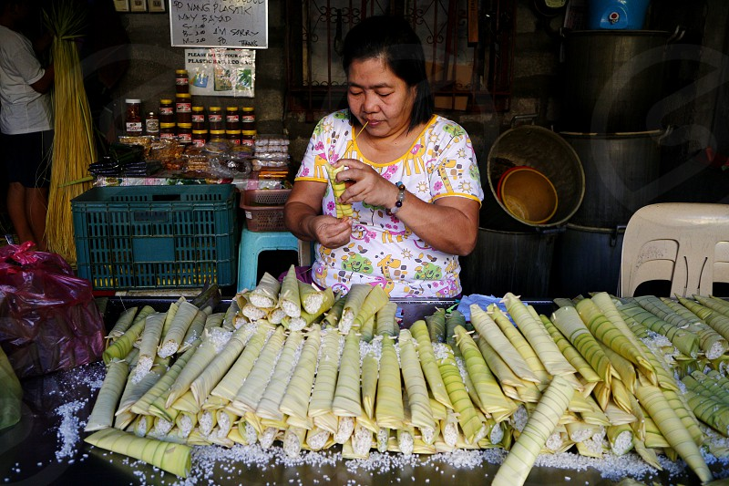 ANTIPOLO CITY PHILIPPINES - MARCH 2 2019: A food vendor wraps raw glutenous rice into palm leaves as she prepares to steam it and cook it into a Filipino delicacy called Suman. photo