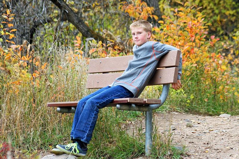 boy sitting on a park bench photo