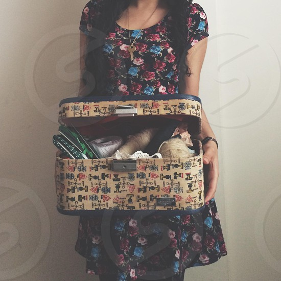 woman holding a hand woven box full of stugff photo