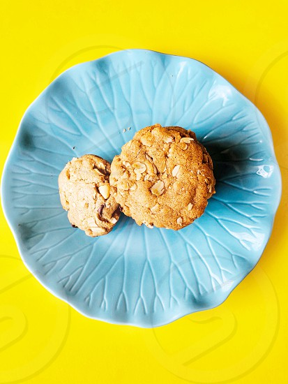 Aqua flower plate on yellow background holding the chocolate chip cookies made with oats coconut oil and whole wheat flour. photo