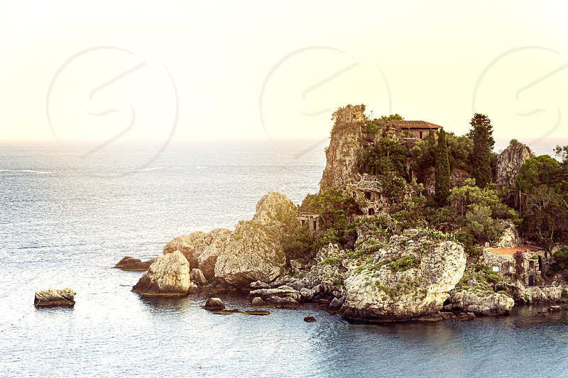 Isola bella islet in the bay of Taormina in Sicily at sunset. Sea and summer season. Tourist destination in Italy photo