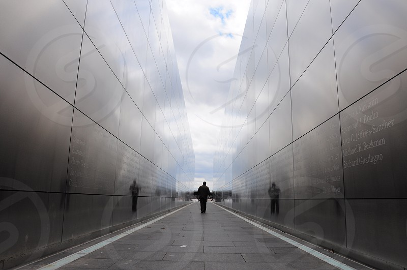 person walking in alleyway between gray walls photo
