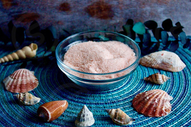 Himalayan pink salt and seashells  on a turquoise surface against a white-washed wood background  photo
