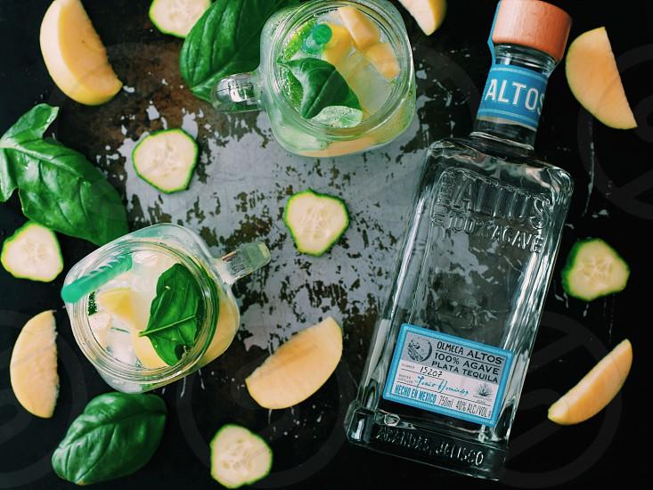 clear glass bottle near clear glass jar mug with lemon juice photo