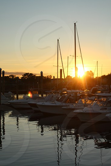 white sailboats and white speedboats on pier under orange sunset photo