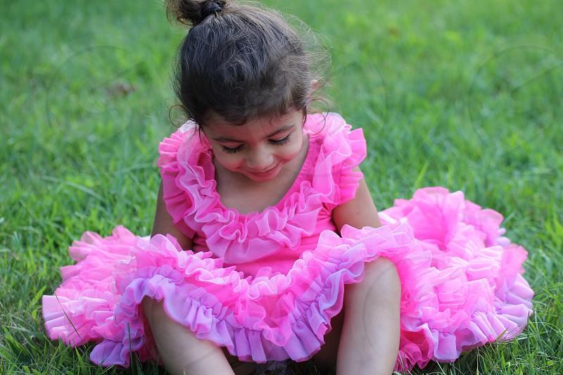 girl in pink ruffled dress sitting on green grass photo