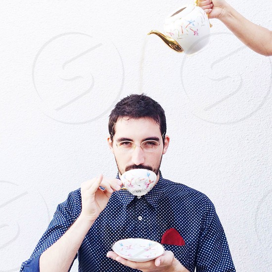 man in blue white button down polka dotted shirt sipping tea with gold white tea pot being poured over his head photo