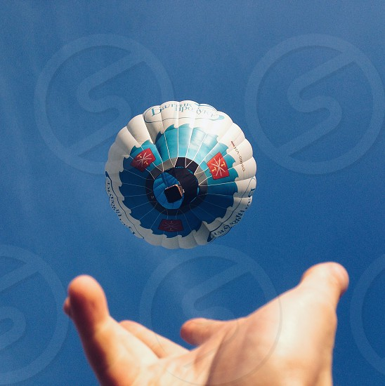 human hand reaching for a blue and white hot air balloon in a blue sky photo