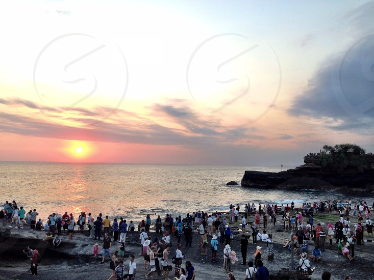 people watching sunset at beach photo