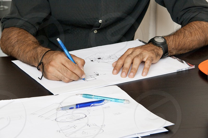 man sitting on chair doing sketch in work time during daytime photo