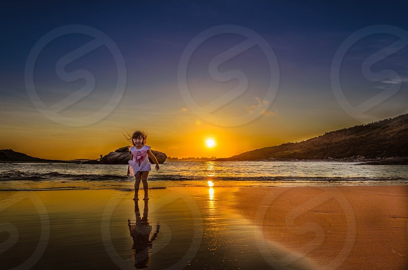 girl standing beside beach with sunset view photo