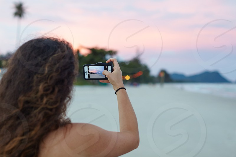 person holding black touchscreen smartphone on beach photo