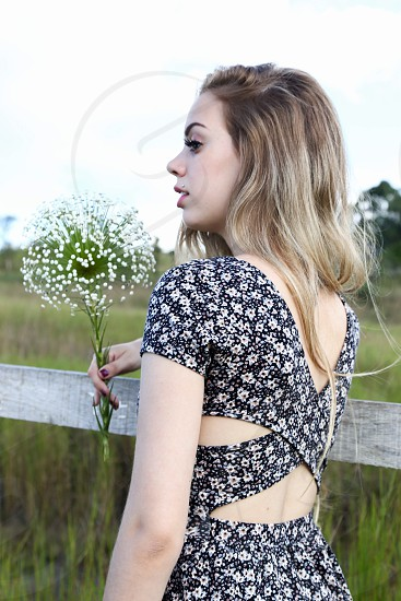 woman with blonde hair holding baby's breath bouquet in black and white ditsy floral cutout back dress on fence photo