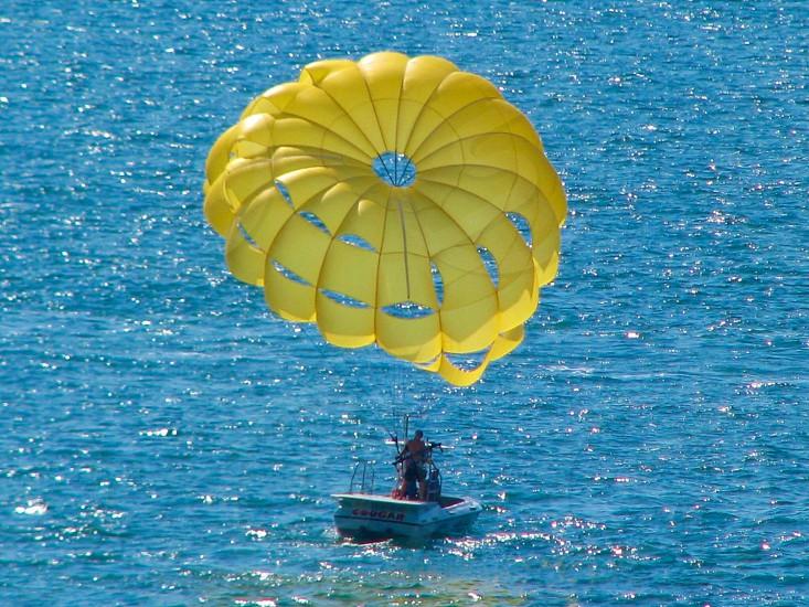 Boat parasail sail sailing boating ocean sea water sky yellow parachute vacation holiday USA America photo