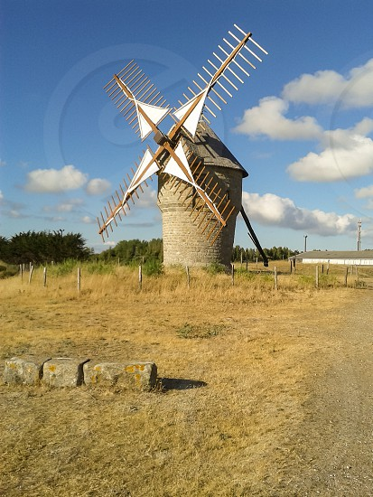 A windmill used to make flour ; nowadays the windmill is only open for tourists visiting Brittany in France. photo