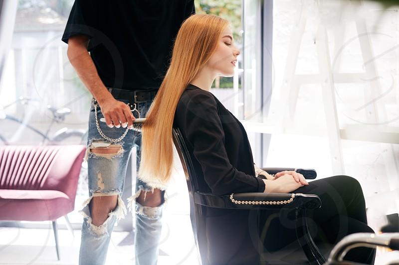 Pretty girl doing hair cut on hairdresser shop photo
