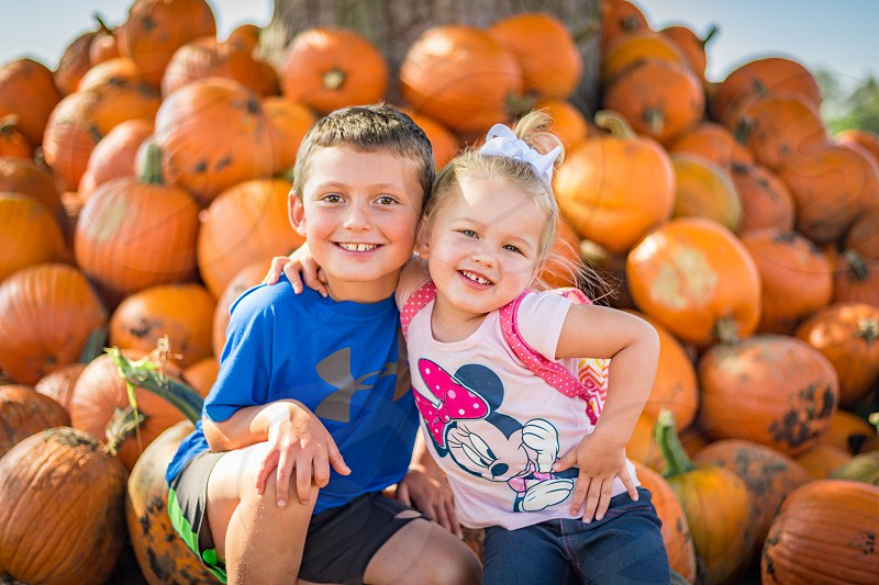Little boy and little girl posing for picture in front of pumpkins at a pumpkin farm during the fall time. Boy aged 7 and girl aged 3. photo
