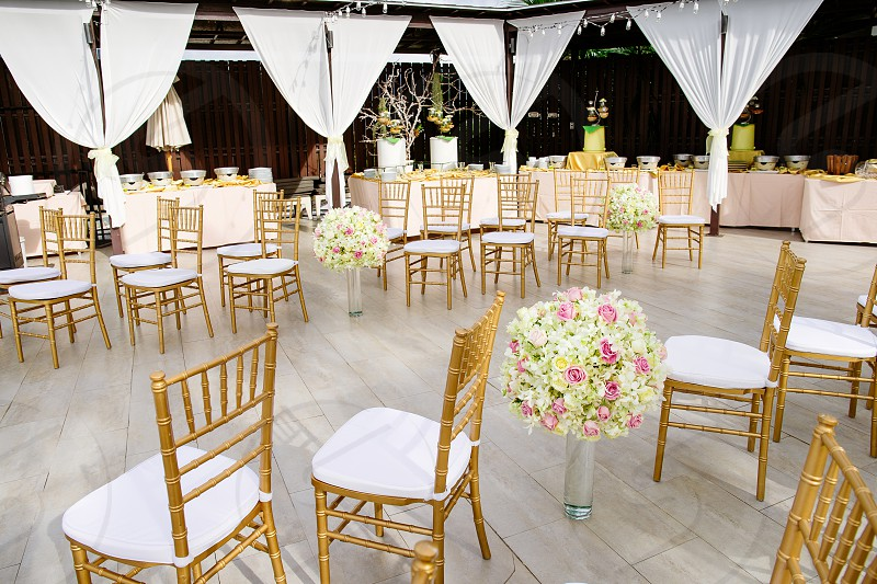 Gold chiavari chairs arrangement with flower bouquet on the glass vase decoration at the aisle for wedding venue The food buffet in background photo