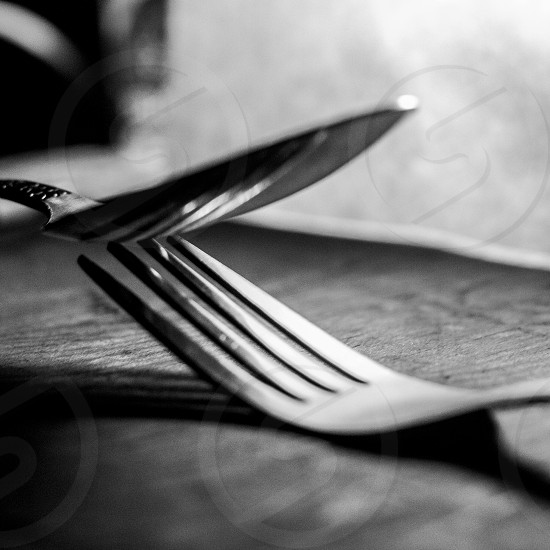 silhouette of stainless spoon and pork over tabletop beside white textile photo