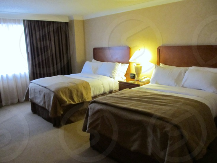 Hotel room with two beds beige walls and mauve brown bedspreads and curtains photo