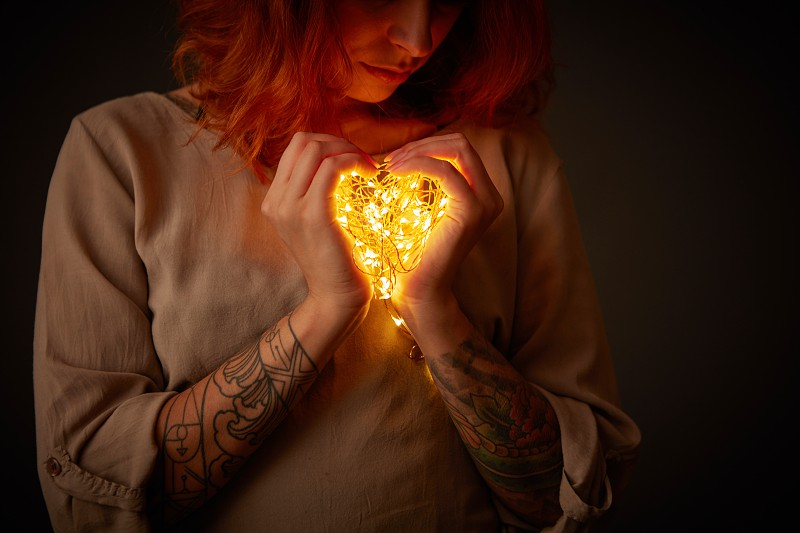 A cute girl with a tattoo is holding yellow garland lights in the shape of a heart in the dark. St. Valentine's Day photo