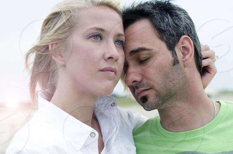 woman in white dress shirt beside a man in her arms in green crew neck shirt photo