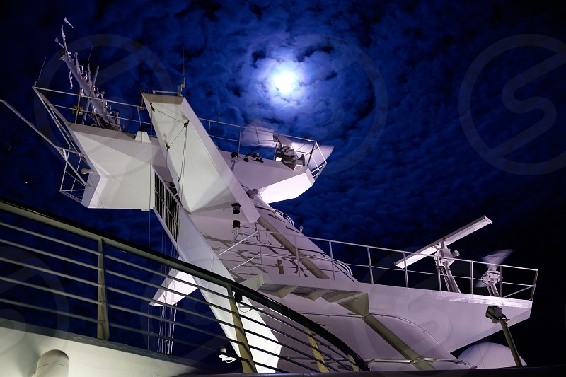 Looking up from ships deck to the bridge tower with the moon behind. photo
