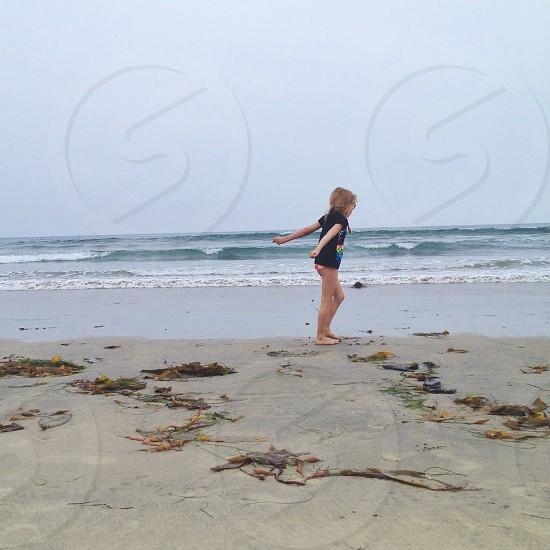 girl standing on seashore photo
