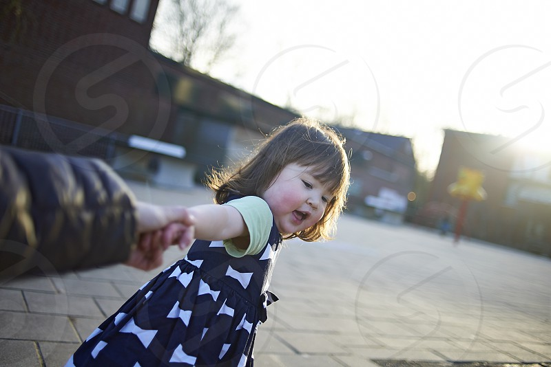 Point of view of a mother as her little Japanese daugther pulls her hand to come to the playground photo