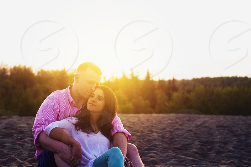 Young couple sitting in the sand during a sunset in summer in Alaska.  photo