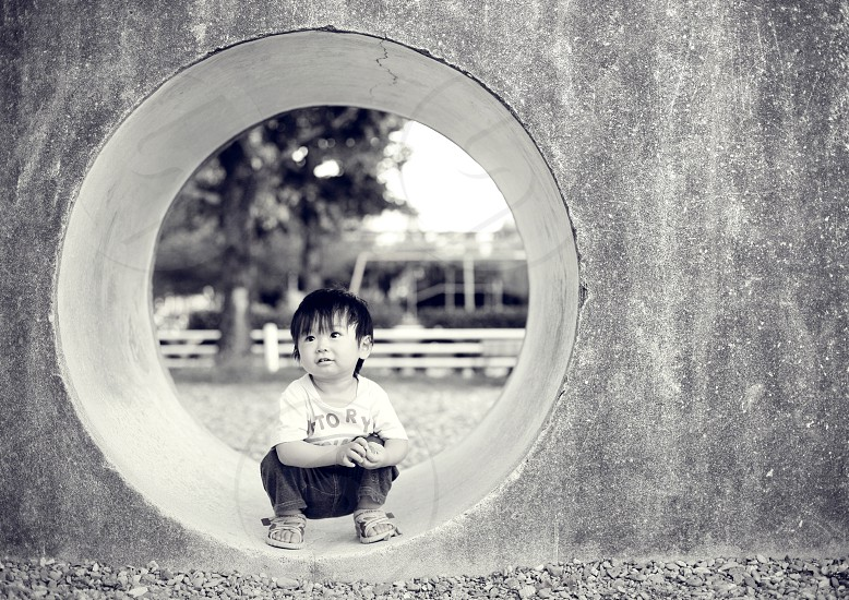 boy wearing a white graphic t shirt crouching in a concrete ring photo