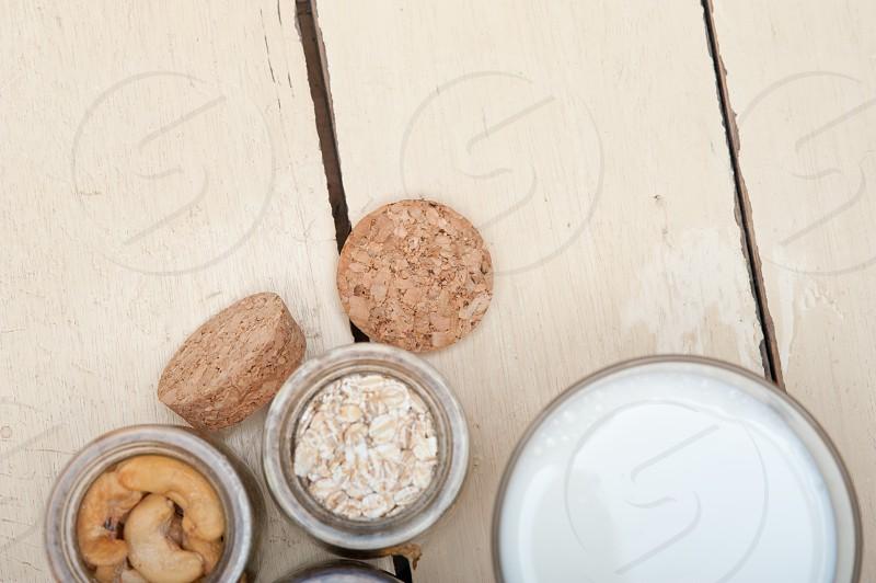 healthy breakfast ingredients milk oat cashew nuts dried cramberry craisinns  photo