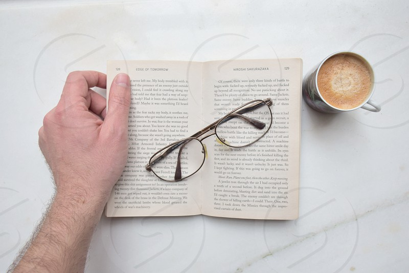 person holding eyeglass over open book beside mug of coffee photo