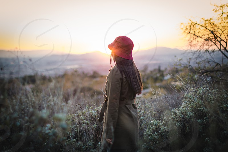 woman in gray trench coat wearing bucket hat facing the mountaintop photo