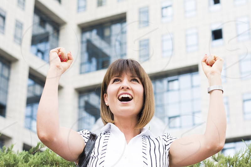 Woman happy with her hands up after a business success photo
