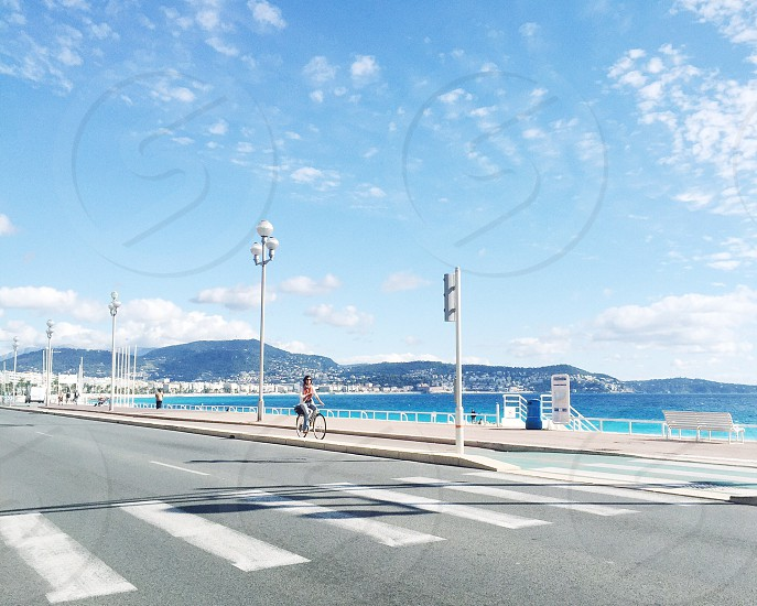 person riding bicycle on road near sea and mountain photo