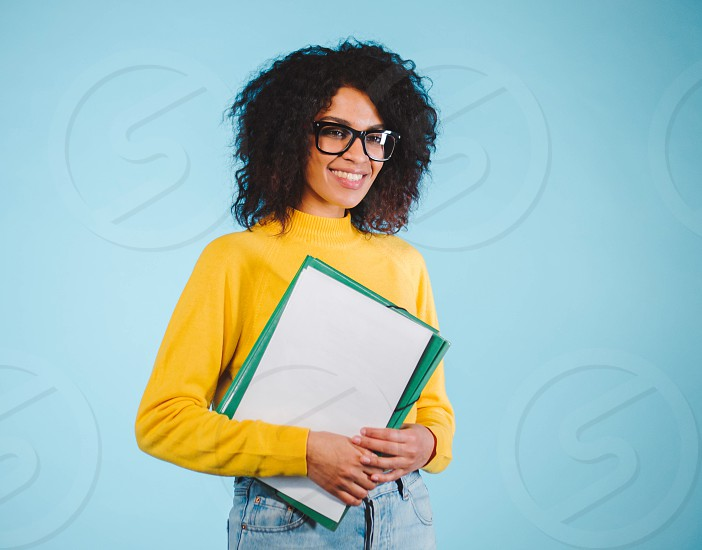 Portrait smiling young african woman in glasses holding folder over blue background. Education concept. photo