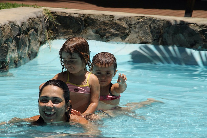 woman with children on back swimming in pool photo